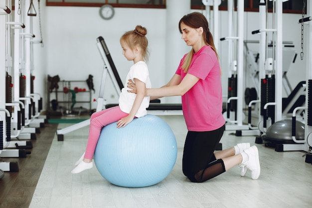 Mother with little daughter are engaged in gymnastics in the gym