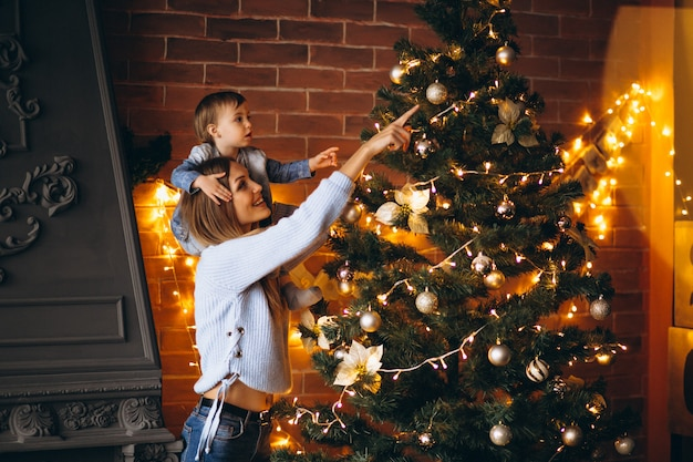 Mother with little daughter decorating christmas tree