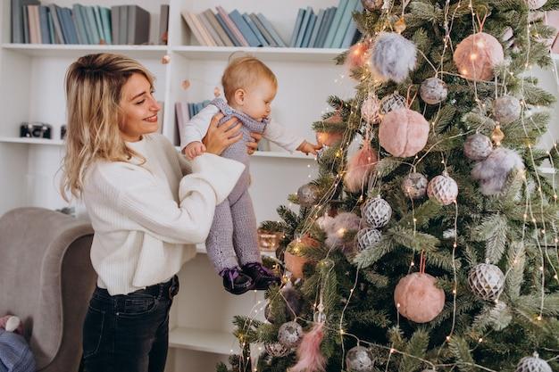 クリスマスツリーにおもちゃをぶら下げ小さな娘を持つ母