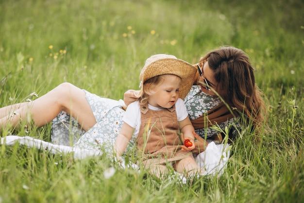 公園でピクニックを持つ小さな娘を持つ母