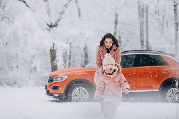 Мама с маленькой дочкой в зимнем парке на машине