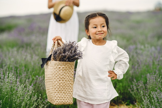 Mother with little daughter on lavender field. beautiful woman and cute baby playing in meadow field. family holiday in summer day.