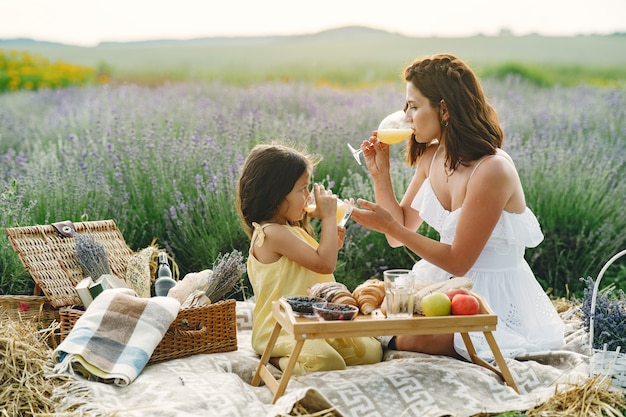 Mother with little daughter on lavender field. beautiful woman and cute baby playing in meadow field. family in a picnic.