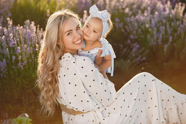 Мать с маленькой дочерью на поле лаванды. красивая женщина и милый ребенок, играя в луговом поле. семейный отдых в летний день.