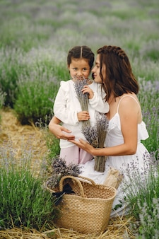 라벤더 밭에 작은 딸과 어머니입니다. 아름 다운 여자와 초원 필드에서 귀여운 아기. 여름날 가족 휴가.