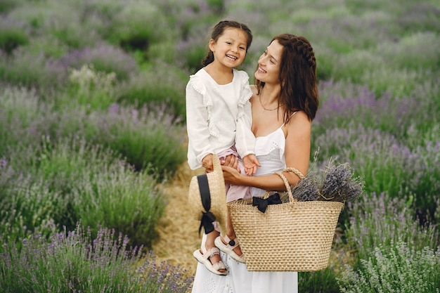 ラベンダー畑に小さな娘を持つ母。美しい女性と牧草地で遊ぶかわいい赤ちゃん。夏の日の家族の休日。