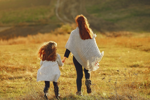 Mother with little daughter playing in a autumn field