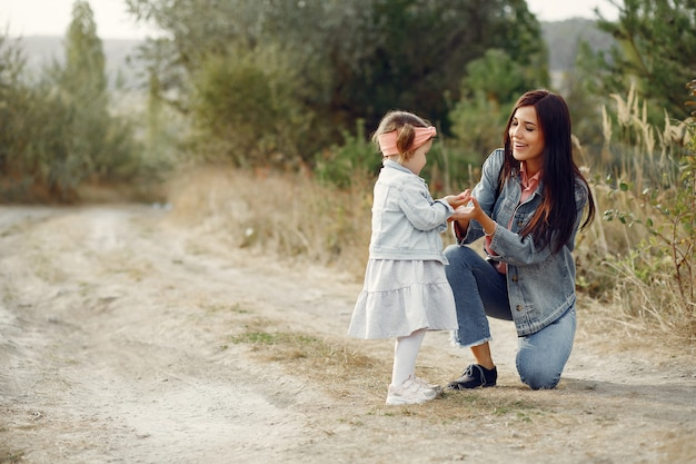 Mother with little daughter playing in a field