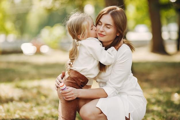 Мать с маленькой дочкой, играя в парке летом