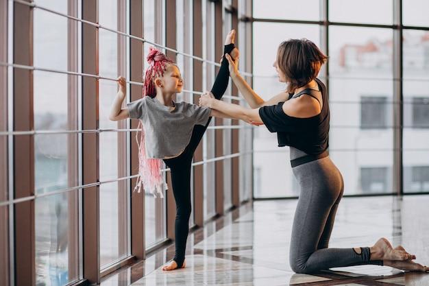 ウィンドウでヨガの練習の小さな娘を持つ母
