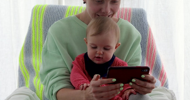 Mother with little daughter seats near the window and uses smartphone on chair