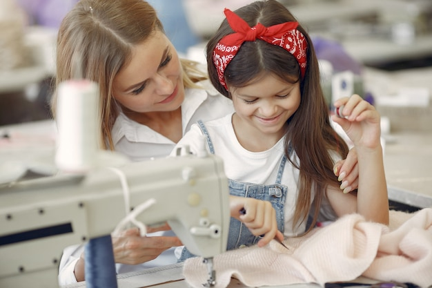 小さな娘を持つ母は工場で服を縫う