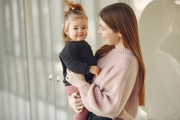ホールに立っている小さな娘を持つ母
