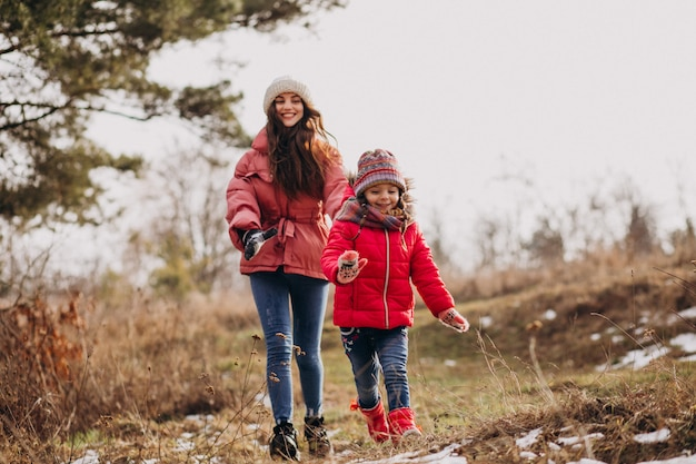 Mother with little daughter in a winter forest