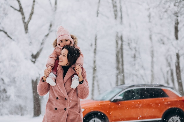 Mother with little daughter in a winter park by car