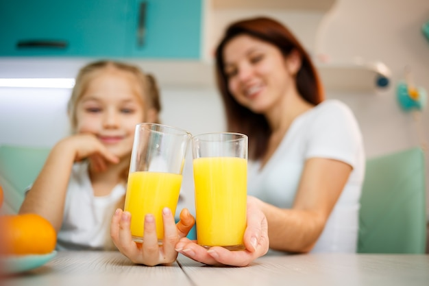 함께 아침을 먹는 동안 오렌지 주스를 마시는 어린 소녀와 어머니