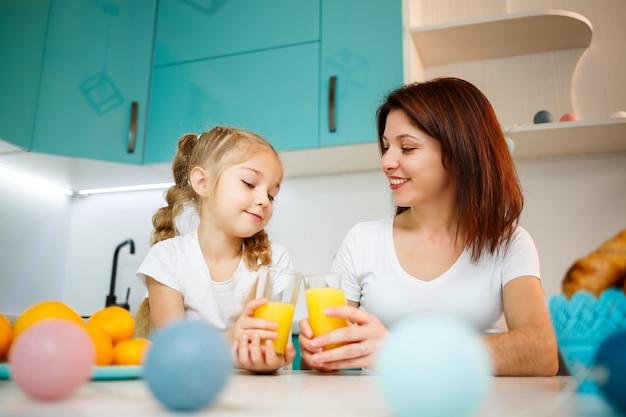彼らが一緒に朝食をとっている間、オレンジジュースを飲む少女と母親