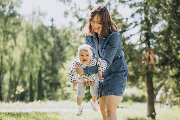 公園で遊んでいる小さな女の子と母