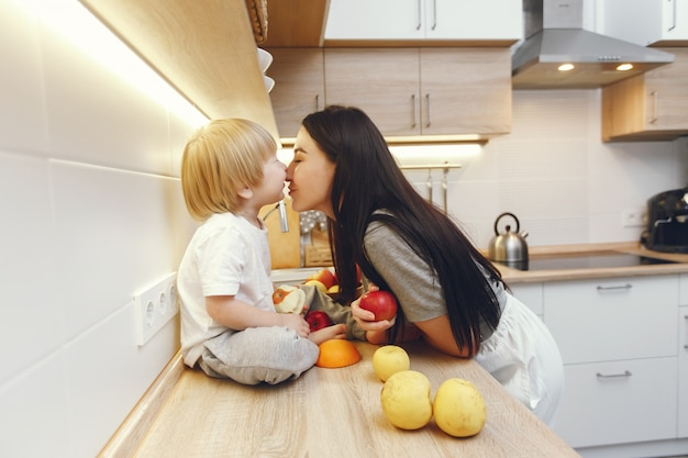 Mother with little son eating fruits in a kitchen
