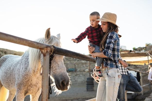 Мать с маленьким сыном развлекаются на лошади на ферме ранчо - внимание мамы