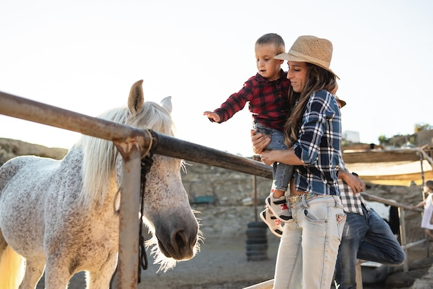 Mother with little son having fun a horse at farm ranch - focus on mom face