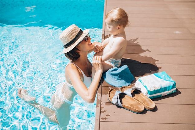 Мама с маленьким сыном веселятся в бассейне