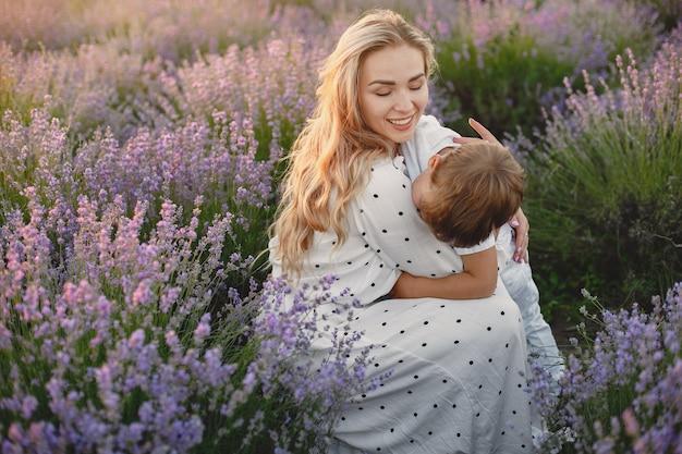 Madre con figlio piccolo sul campo di lavanda. bella donna e bambino sveglio che giocano nel campo del prato. vacanze in famiglia in una giornata estiva.