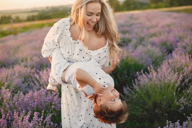 Mother with little son on lavender field. beautiful woman and cute baby playing in meadow field. family holiday in summer day.