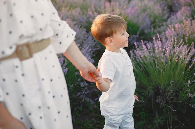 라벤더 밭에 작은 아들과 어머니입니다. 아름 다운 여자와 초원 필드에서 귀여운 아기. 여름날 가족 휴가.