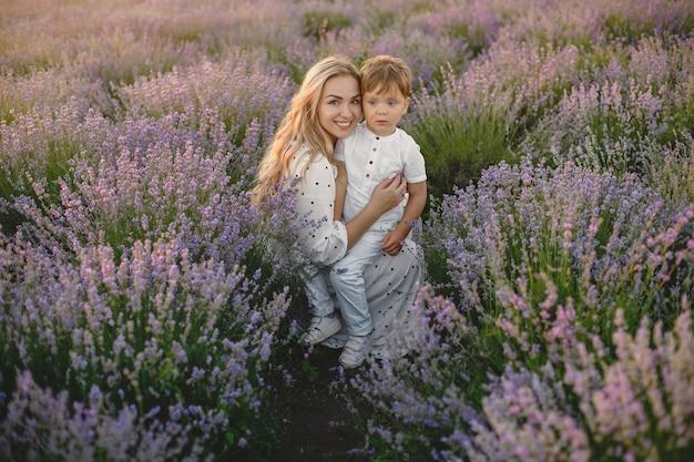ラベンダー畑に幼い息子を持つ母。美しい女性と牧草地で遊ぶかわいい赤ちゃん。夏の日の家族の休日。