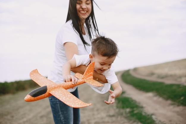 장난감 비행기를 가지고 노는 작은 아들과 어머니