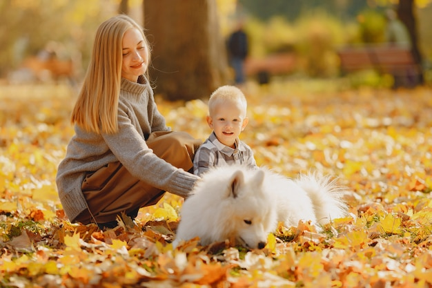 Mother with little son sitting in a autumn field
