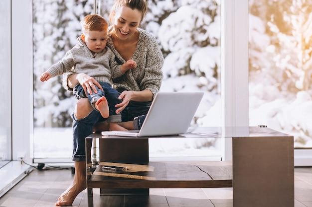 집에서 컴퓨터에서 작업하는 작은 아들과 어머니