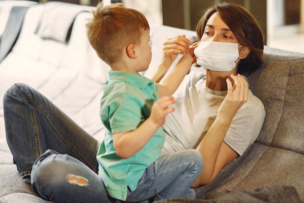 検疫で自宅で座っている小さな息子を持つ母