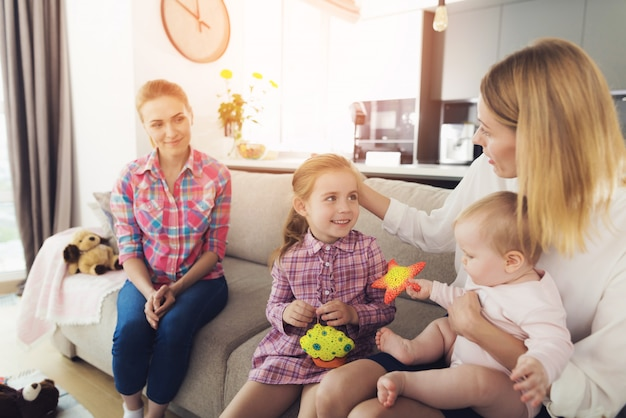 Mother with lovely kids sits on couch near nanny