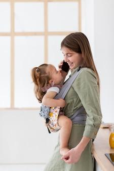 Мать с телефоном держит ребенка