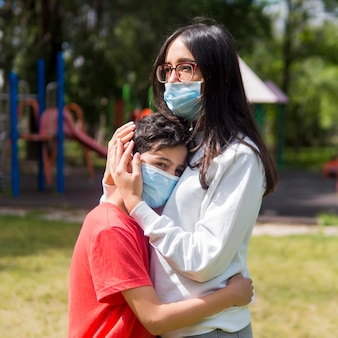 Mother with reading glasses hugging her son