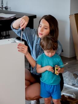 드라이버와 아이가있는 어머니는 가구를 설치하고 있습니다.