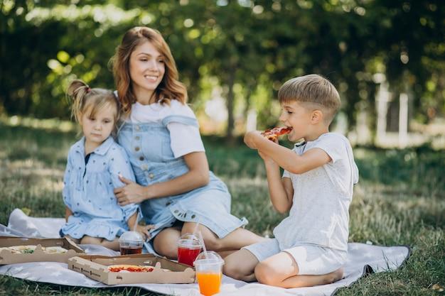 Мать с сыном и дочерью едят пиццу в парке