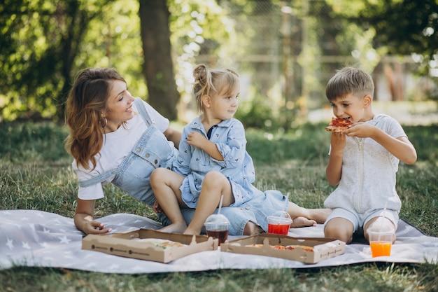 아들과 딸이 공원에서 피자를 먹는 어머니