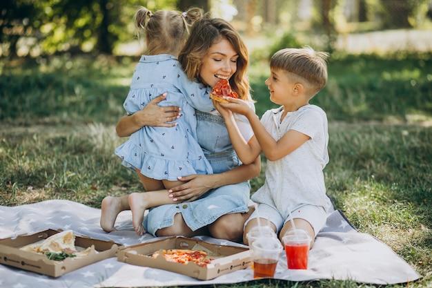 息子と公園でピザを食べる娘を持つ母