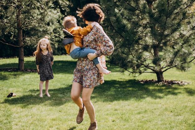 Мать с сыном и дочерью веселятся на заднем дворе