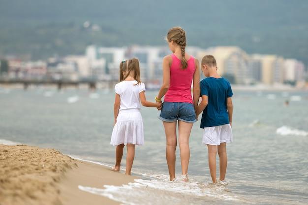息子と砂のビーチで一緒に歩く娘を持つ母
