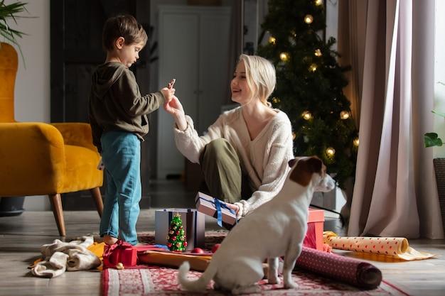 아들을 둔 어머니가 집에서 바닥에 크리스마스 선물을 포장하고 있습니다.