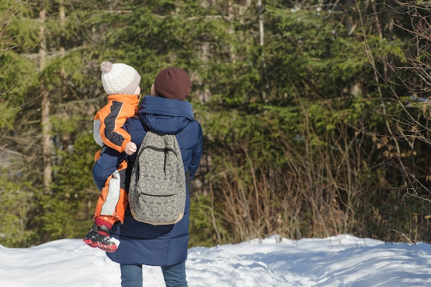 Mother with son in arms and backpack stands against the background of coniferous forest