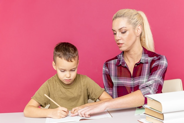 Мать с сыном дома вместе делают домашнее задание во время карантина.