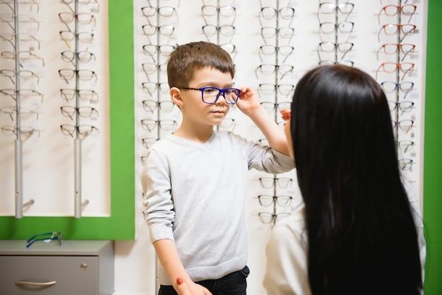 광학 상점에서 안경을 선택하는 아들과 함께 어머니.