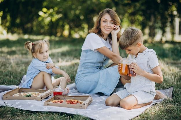 Madre con figlio e figlia che mangiano pizza nel parco