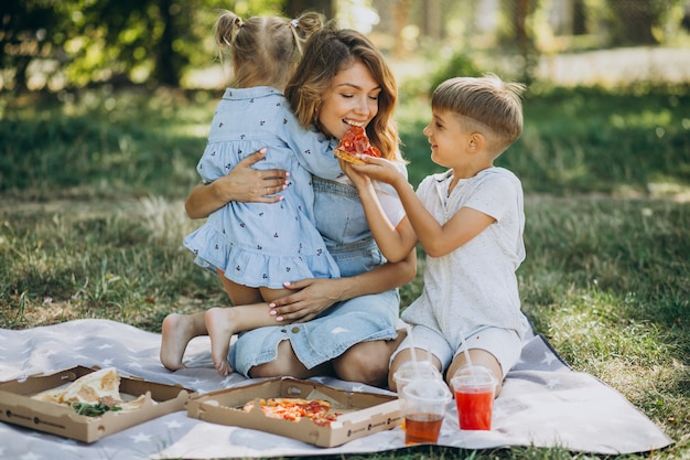 Mother with son and daughter eating pizza in park