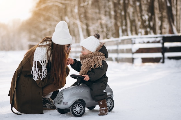 Mother with son in little car outside in winter